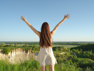 Young woman stands with her arms raised up to the sky.