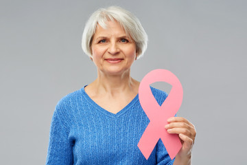 health, charity and old people concept - portrait of smiling senior woman with pink breast cancer awareness ribbon over grey background