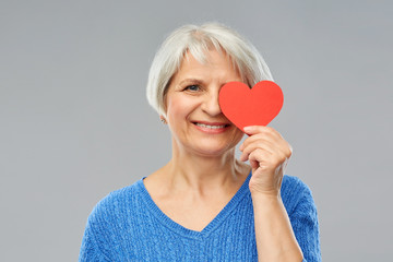 valentine's day, summer and old people concept - portrait of smiling senior woman covering one eye with red heart over grey background