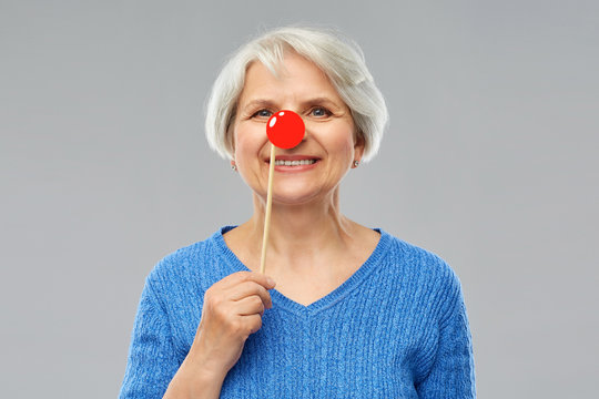red nose day, party props and photo booth concept - portrait of smiling senior woman in blue sweater with clown nose over grey background