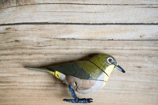 Vogel in grün und gelb als Dekoration auf hölzernem Hintergrund