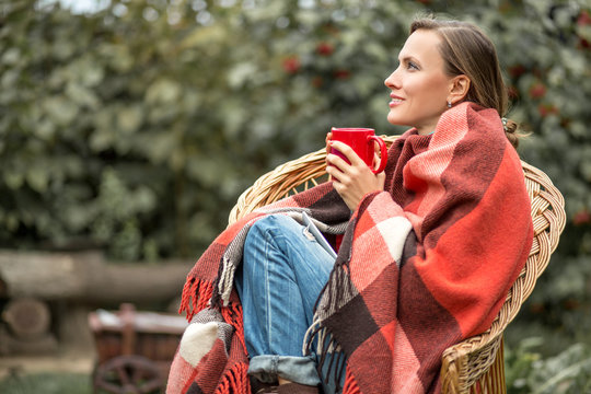 Beautiful girl resting and drinknig coffee sitting in autumn garden in a chair wrapped in a plaid woolen blanket