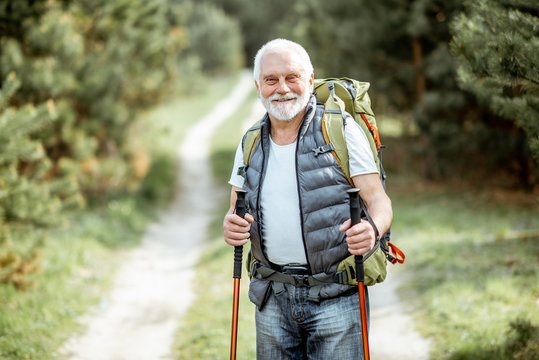Portrait of a senior man with backpack and trekking sticks on the way in the woods