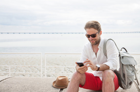 Tourist man with backpack looking at mobile phone outdoor by the sea.