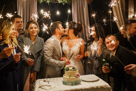 young beautiful wedding couple cut wedding cake with friends and have fun with bengal lights