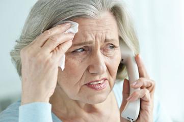 Close-up portrait of upset senior woman calling doctor