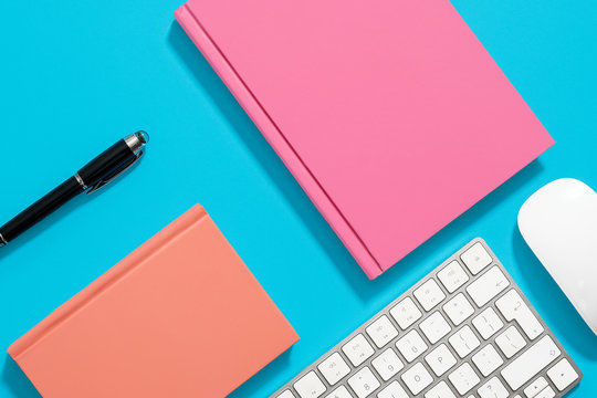 Orange and pink hardcover notebooks lying flat on a pastel blue background with an iMac keyboard and mouse with a black pen.