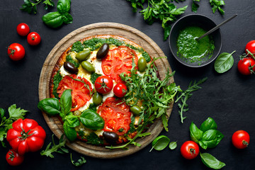 Pizza with green pesto and fresh tomatoes