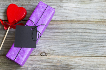 Purple present box offered with love, near red heart shape on wooden background