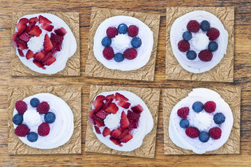 Appetizing pavlova cakes with meringue and fruits as strawberries, blueberries and raspberries, aerial view