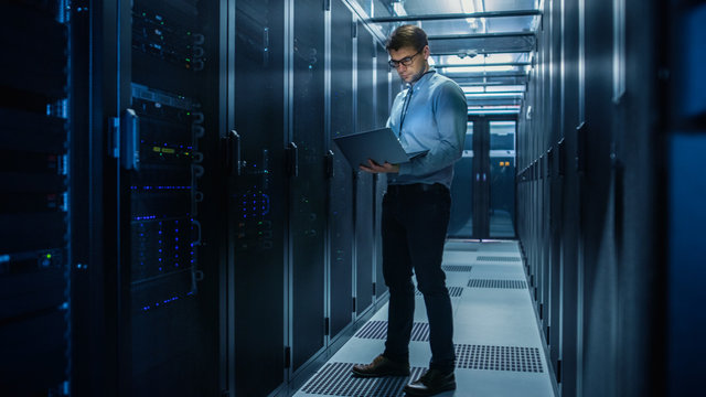 In Data Center IT Engineer Stands Before Working Server Rack Doing Routine Maintenance Check and Diagnostics Using Laptop. Concept of Cloud Computing, Artificial Intelligence, Supercomputer