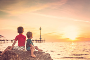 Two boys sitting on the rock at the beach at sunset