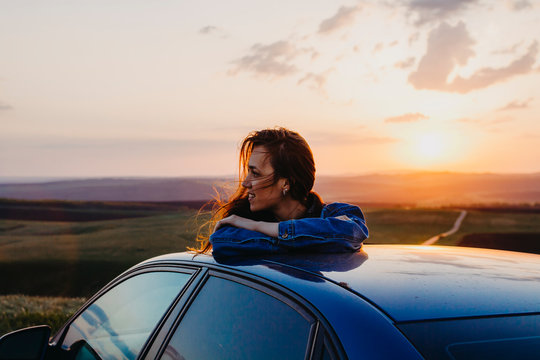 Woman standing leaning on the car at sunset