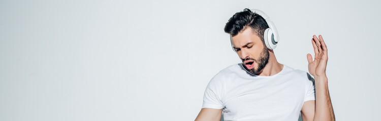 panoramic shot of handsome man listening music in headphones and singing on white