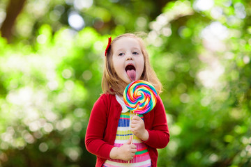 Little girl with colorful candy lollipop