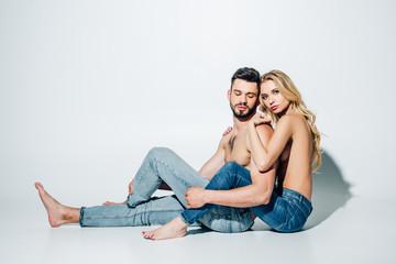 attractive blonde girl hugging shirtless boyfriend while sitting on white