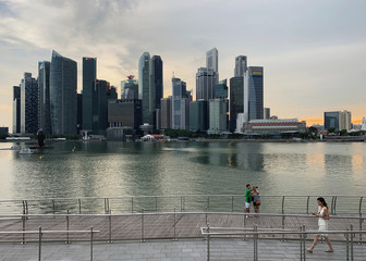 A passer-by looks at her mobile phone as people take a selfie photo using a smartphone, with Singapore's central business district skyline, in Singapore