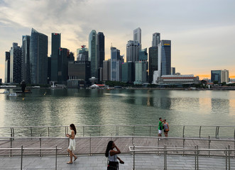 Passers-by hold their mobile phones as people take a selfie photo using a smartphone, with Singapore's central business district skyline, in Singapore