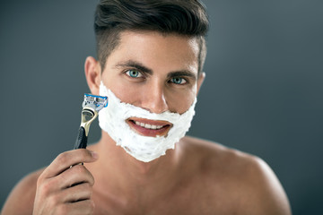 young man shaving his beard with razor