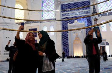 Women pose for a selfie picture as they visit Grand Camlica Mosque on the first Friday of the holy fasting month of Ramadan in Istanbul