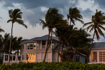 Coast house beachfront waterfront vacation home, house during evening sunset with nobody in Florida, gulf of mexico, stormy weather and wind on palm trees