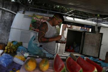 A vendor sells fruit at a street market in Rio de Janeiro