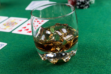 Glass of Scotch on Ice on the poker table with cards and chips