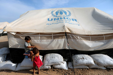 Venezuelan migrant children play next to a tent, in a camp run by the UN refugee agency UNHCR in Maicao