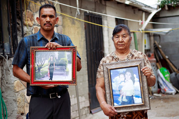Abel Arredondo and Maria del Carmen Vazquez pose for a picture as they hold the photographs of their daughter Esther Arredondo Vazquez, a migrant living in Canutillo, Texas, U.S., in Ciudad Juarez
