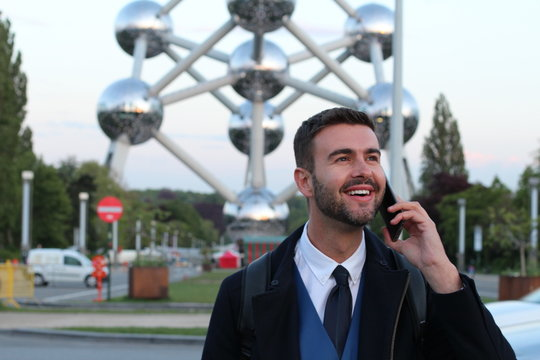 Handsome European businessman calling by phone outdoors