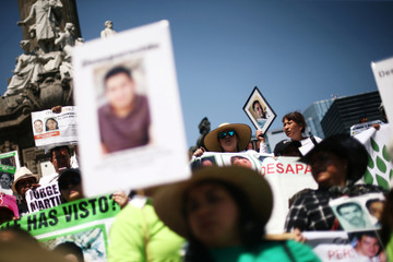 Mothers and relatives hold pictures of missing people during a march to demand justice for their missing relatives on Mother's Day in Mexico City