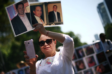 A woman holds pictures of missing people as mothers and relatives march to demand justice for their missing relatives on Mother's Day in Mexico City