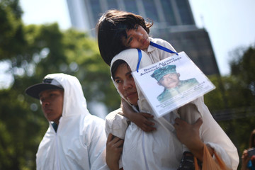 A woman and a boy hold a picture of a missing person as mothers and relatives march to demand justice for their missing relatives on Mother's Day in Mexico City