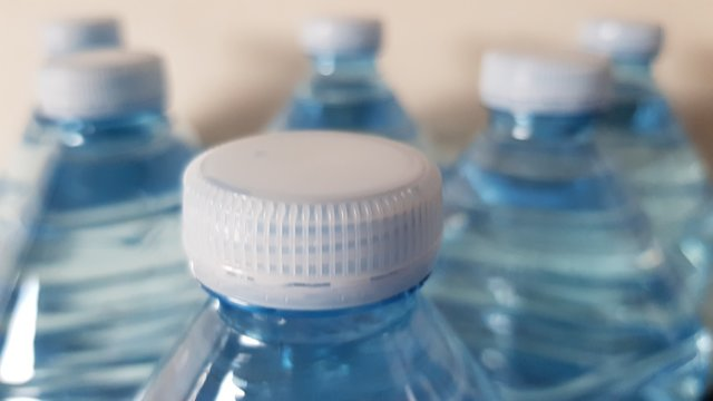 plastic bottles focused on the first row of caps.
