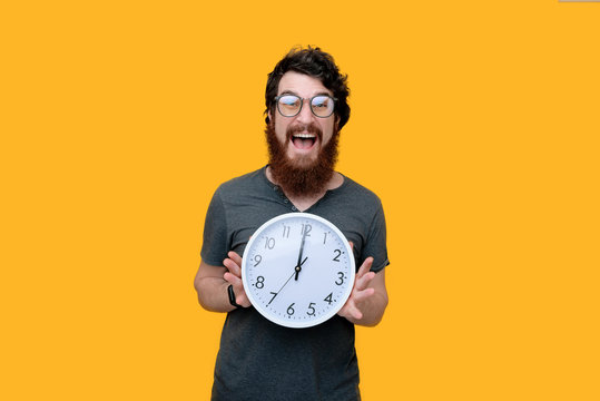 Excitd bearded guy with galsses, holding a clock, standing over yellow background