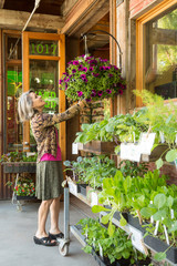 Happy, smiling middle-aged woman customer shopping for flowers plants at a garden center shop store
