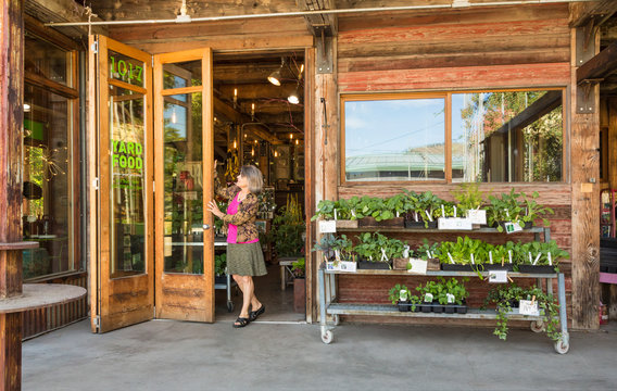 Happy, successful, middle-aged woman small business owner opening front doors of garden center shop store