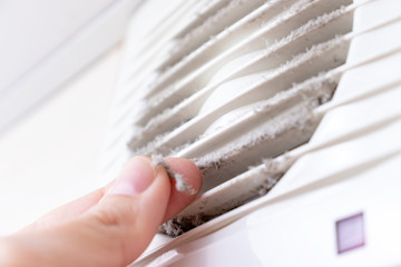 Extremely dirty and dusty white plastic ventilation air grille at home close up and a hand holding dust by fingers, harmful for health