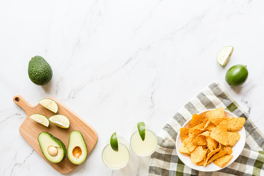 Fresh avocado, lime, drink and nacho chips lying on marble background. Recipe for Cinco de Mayo party. Top view, overhead, flat lay, copy space
