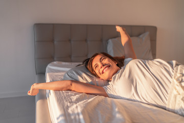 Happy girl waking up in the morning sunshine looking at sunrise sun in window excited to enjoy the day. Wake up energetic Asian woman lying in bed well rested from a good night sleep. Fotomurales