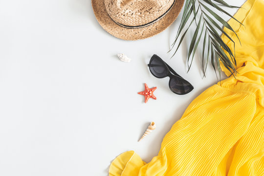 Summer composition. Tropical leaves, dress, hat on gray background. Summer concept. Flat lay, top view, copy space