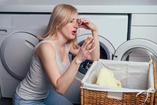 blonde female next to washing machine dirty laundry basket