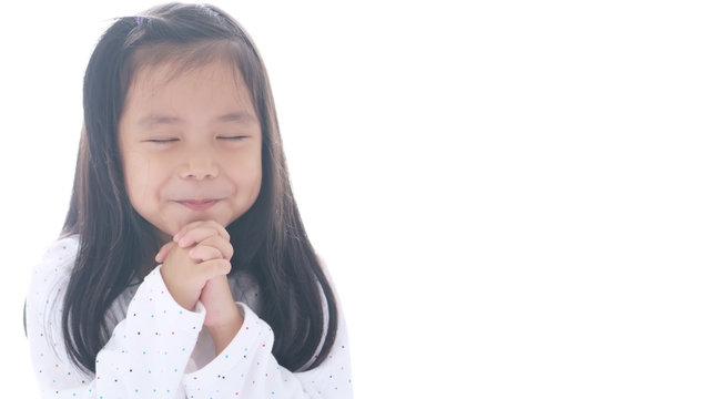 Asian child cute or kid girl smiling with hold hand and pray or beg and sorry for peaceful world and happy with wear white clothes on white space background isolated and wide screen