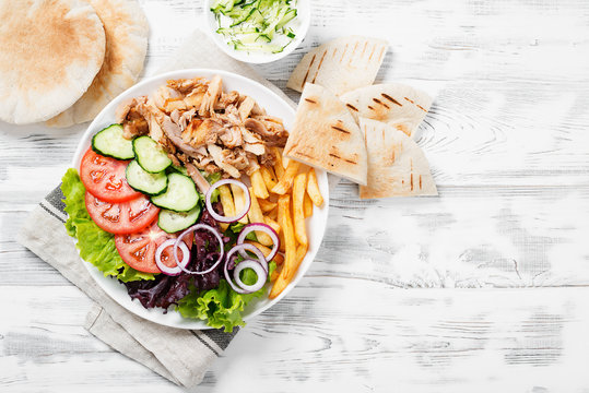 Doner kebab or gyros on a plate with french fries, pita bread and salad.