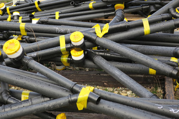 stack of black pipe tubes hold together with yellow tape