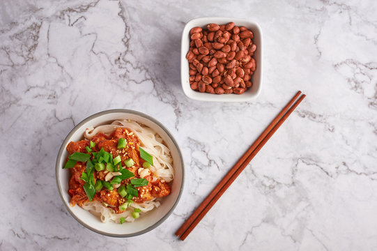 shan noodles with peanuts and chopsticks at white marble tabletop. burmese cuisine traditional dish. myanmar food. rice noodles with pork in tomatos