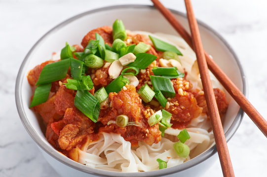 shan noodles with chopsticks at white marble tabletop. burmese cuisine traditional dish. myanmar food. rice noodles with pork in tomatos. asian dish.  close up