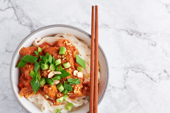 shan noodles with chopsticks at white marble tabletop. burmese cuisine traditional dish. myanmar food. rice noodles with pork in tomatos. asian dish. copy space. top view