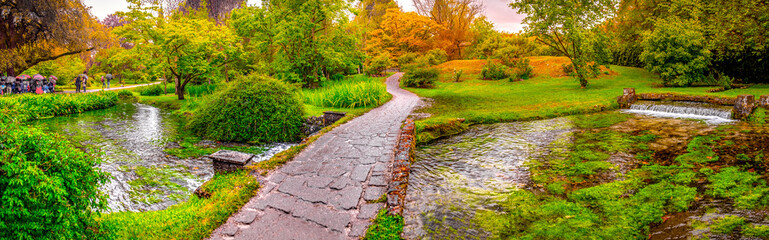 Photo sur Plexiglas Jardin enchanted eden garden bridge over pond in horizontal panoramic Nymph Garden or Giardino della Ninfa in Lazio - Italy