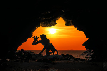 Caveman posture or action in the cave at sunset